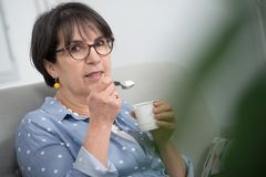 Pretty mature woman eating a yogurt at home royalty free stock photos