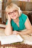 Pretty mature woman in glasses reading magazine Stock Photos