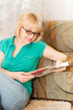Pretty mature woman in glasses reading magazine Stock Photos