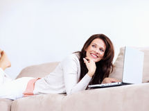 Pretty mature woman with a laptop on couch Royalty Free Stock Images