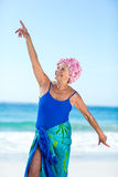 Pretty mature woman raising her arms on the beach Stock Photos