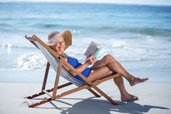 Pretty mature woman reading a book lying on deck chair Stock Image
