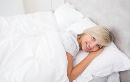 Pretty mature woman resting in bed Royalty Free Stock Photos