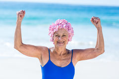 Pretty mature woman showing her muscles on the beach Stock Photos