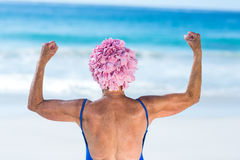 Pretty mature woman showing her muscles on the beach Stock Photography