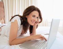 Pretty mature woman using laptop on bed Stock Image