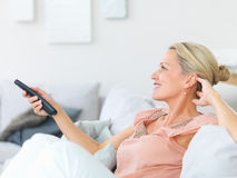 Pretty mature woman watching television Royalty Free Stock Photography