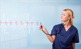 Pretty medical doktor listening to red pulse and heart rates Royalty Free Stock Photography