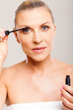 Mid age woman mascara. Pretty mid age woman putting mascara on her eyelashes royalty free stock photography