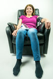Pretty middle-age woman sitting in black leather recliner armchair. Checking blood pressure using portable blood pressure machine. Royalty Free Stock Photo