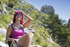 Pretty middle aged female hiker resting on big rock Royalty Free Stock Images