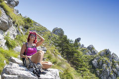 Pretty middle aged female hiker resting on big rock Stock Image