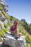 Pretty middle aged female hiker resting on big rock Royalty Free Stock Photo