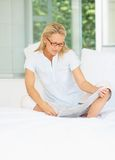 Pretty middle aged woman reading newspaper in bed Stock Photography
