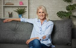 Pretty middle aged woman is sitting on a sofa at home. Pretty middle aged woman is sitting on a sofa stock photography