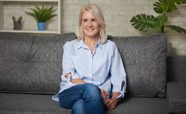 Pretty middle aged woman is sitting on a sofa. At home stock photography