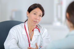 Pretty midle aged doctor talking to patient Stock Images