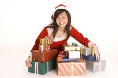 Pretty Miss Santa. A cute asian woman dressed as santa sits with a load of presents stock photos