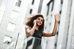 Pretty mixed race businesswoman speak by phone in city. stock photography