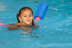 Pretty mixed race child swimming in pool. During summer royalty free stock photography