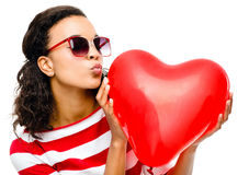 Pretty mixed race girl holding red heart balloon Royalty Free Stock Photos