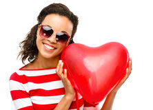 Pretty mixed race girl holding red heart balloon Stock Photo
