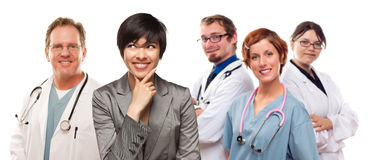 Pretty Mixed Race Woman with Doctors and Nurses Behind Royalty Free Stock Photos