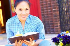 Pretty Mixed Race Woman Reading Holy Bible Stock Photo
