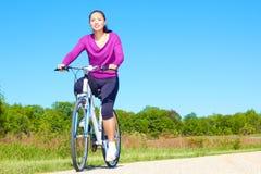 Pretty Mixed Race Woman Riding Bike On The Trail Stock Photo