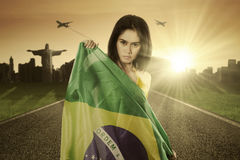Pretty model with Brazilian flag on the road Royalty Free Stock Images