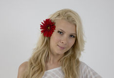 Pretty model with bright red flower in her hair Royalty Free Stock Photos