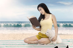 Pretty model with dog reads book at shore. Pretty female model enjoy holiday while sitting on the beach and reading a book with her dog Stock Image