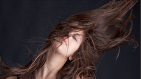 Pretty Model Flinging Hair Wildly. A fun and interesting fashion image of a beautiful young woman flinging her hair about wildly, while looking at the viewer Stock Images