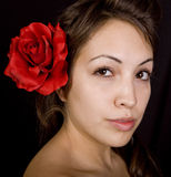 Pretty model with flower in her hair. A pretty model with a red flower in her hair Stock Image