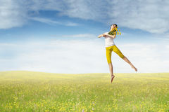 Pretty model with flower jumps on meadow Stock Images
