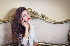 Pretty model girl sitting on victorian sofa posing Royalty Free Stock Image