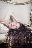 Pretty model girl sitting on victorian sofa posing Stock Photo