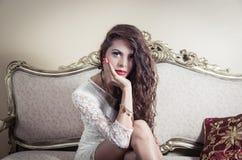 Pretty model girl sitting on victorian sofa posing Royalty Free Stock Photo