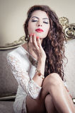 Pretty model girl sitting on victorian sofa posing Stock Images
