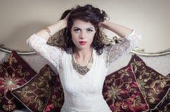 Pretty model girl sitting on victorian sofa posing Stock Photos