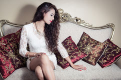 Pretty model girl sitting on victorian sofa posing Royalty Free Stock Photography