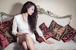 Pretty model girl sitting on victorian sofa posing Royalty Free Stock Photography