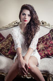 Pretty model girl sitting on victorian sofa posing Royalty Free Stock Images
