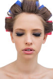 Pretty model with hair curlers closing eyes Royalty Free Stock Photos