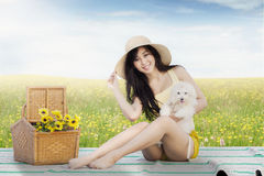 Pretty model with her dog sitting at field Stock Image