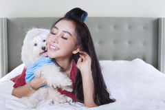 Pretty model and her puppy on bed. Photo of female model with long hair lying in the bedroom while hugging a maltese dog Royalty Free Stock Images