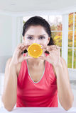 Pretty model holds orange piece Stock Images