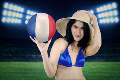 Pretty model holds soccer ball in stadium Stock Photo