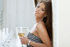 Pretty model with long brown hair posing near wall Stock Image