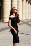 Pretty model with long curly hair and red lips. Young beautiful stylish girl posing at summer city streets on a sunny day. Stunning woman wearing black dress and Stock Image